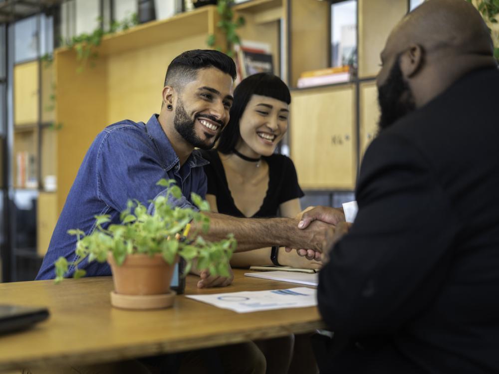 hispanic man shaking hands with black man over desk