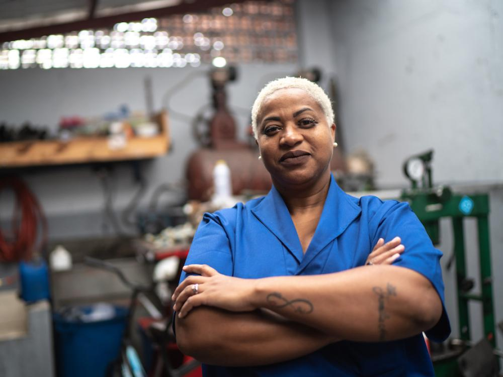 black woman wearing blue shirt in mechanics shop with arms folded