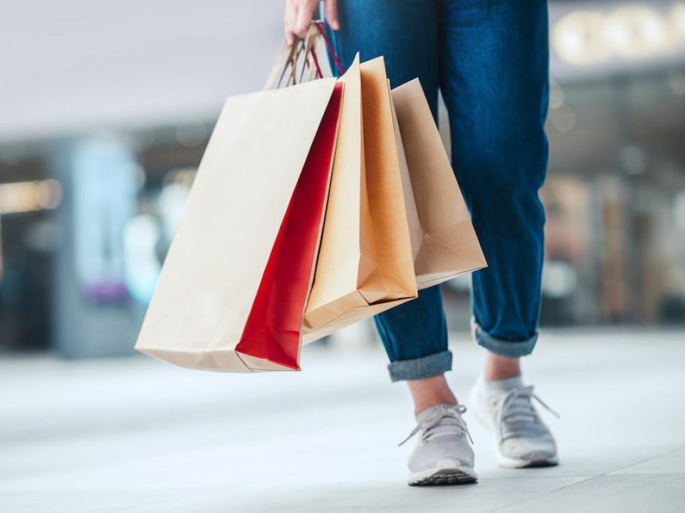 woman wearing jeans holding three brown shopping bags