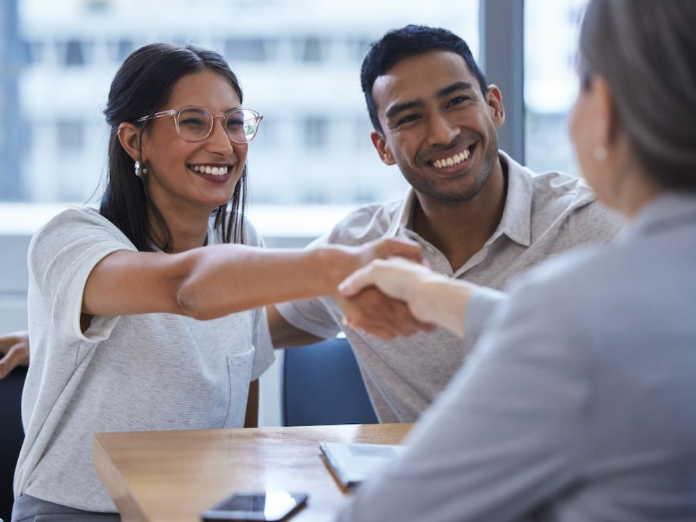 young hispanic couple shake hands with someone in meeting