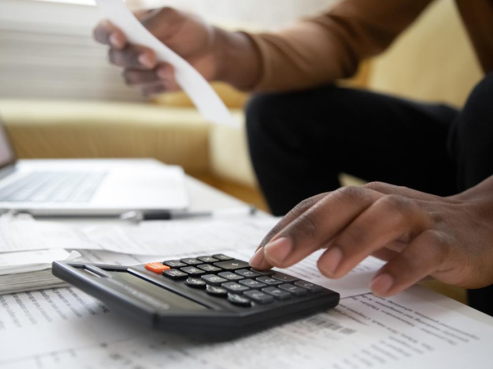 black man using calculator at his computer