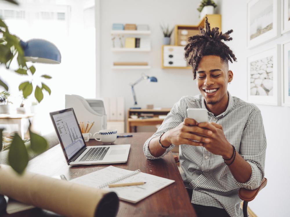 young black man in button down sitting at computer and laughing at phone