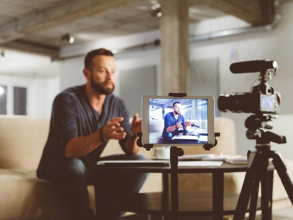man recording video in living space