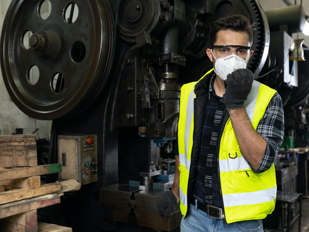 man wearing a hard at and vest in auto shop