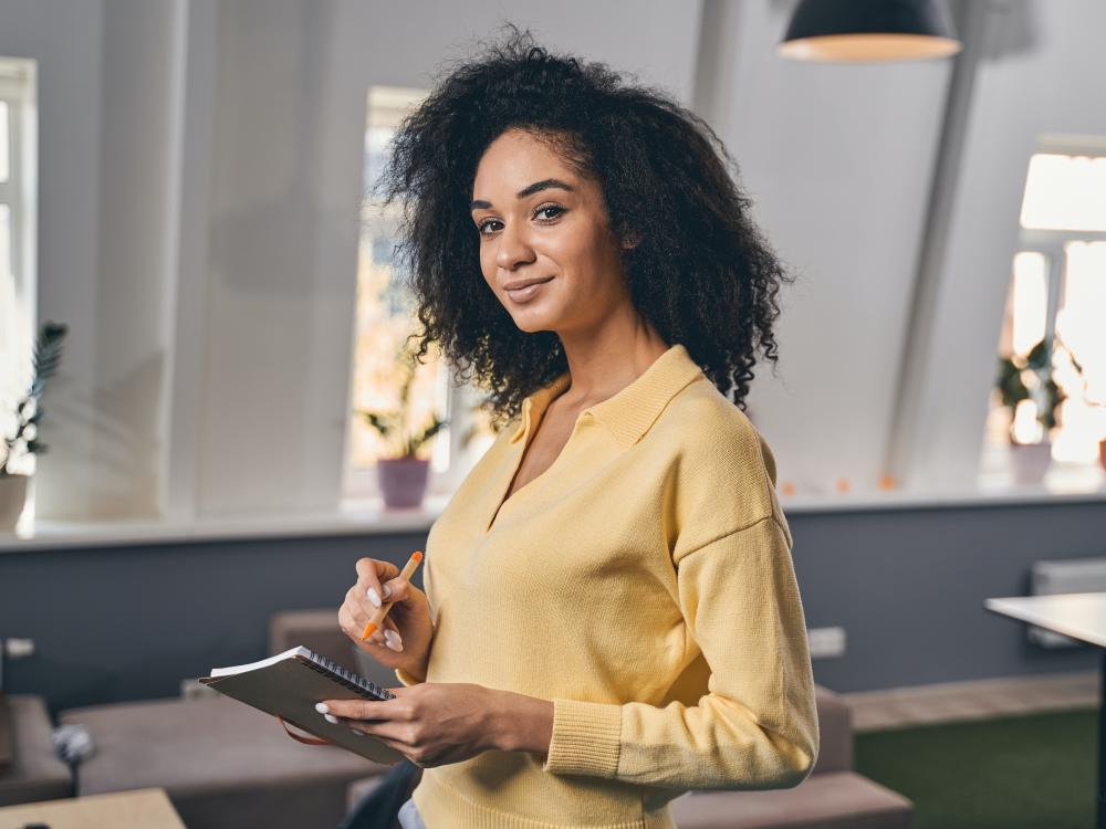 young multi racial woman in yellow shirt holding a notebook and pen