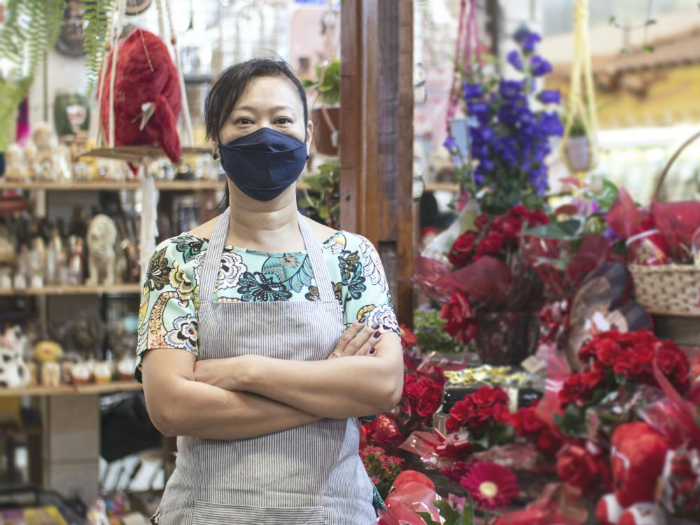 asian woman stands in flower shop wearing a light color floral shirt surrounded by red flowers