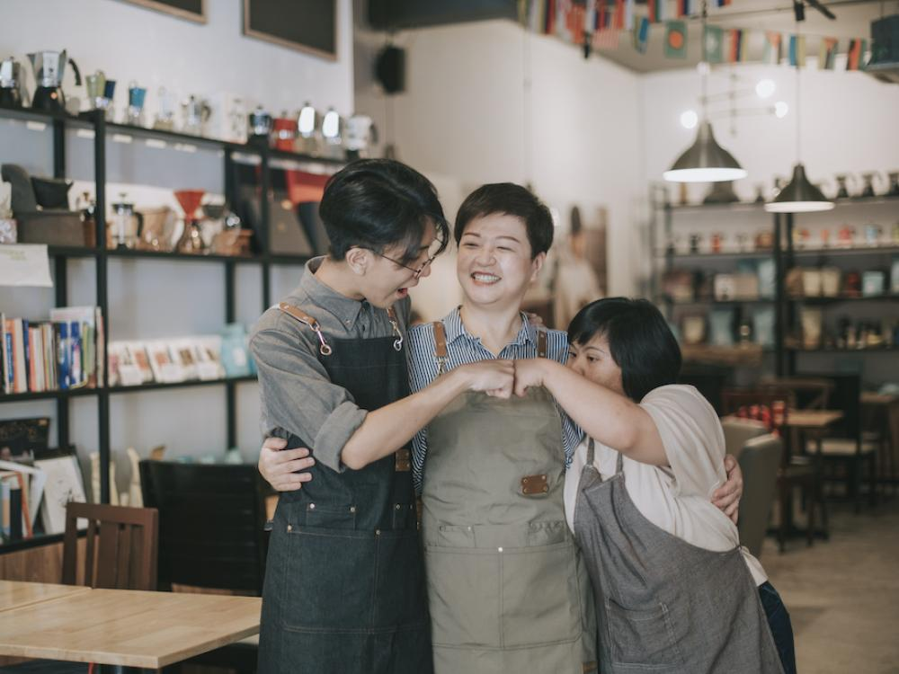 young asian family standing in their business fist bumping each other