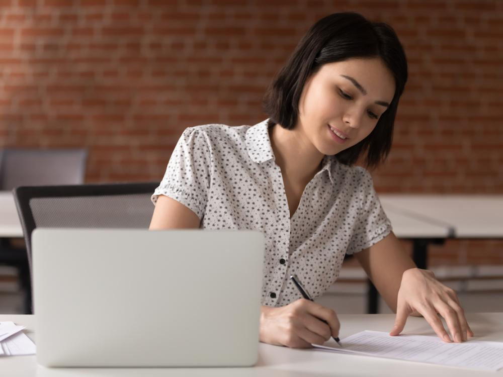 asian woman writing on paper while at her computer