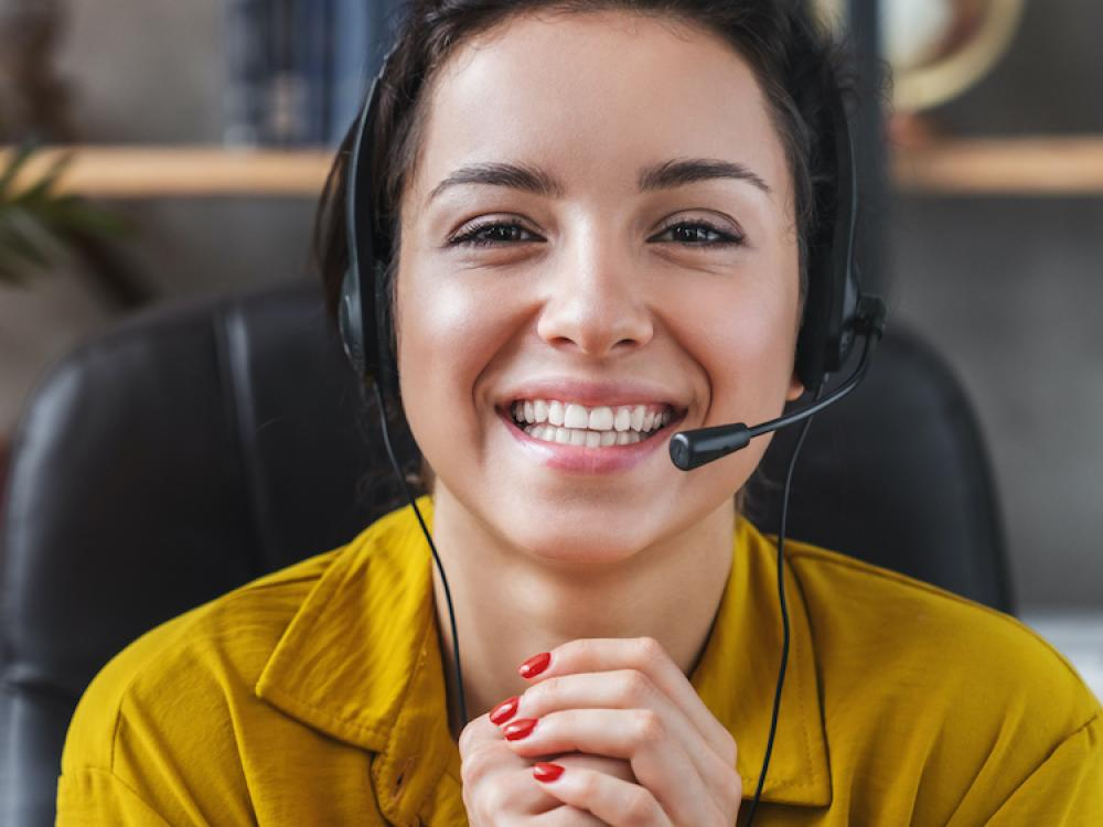 young hispanic woman in yellow sweater smiling with headset on