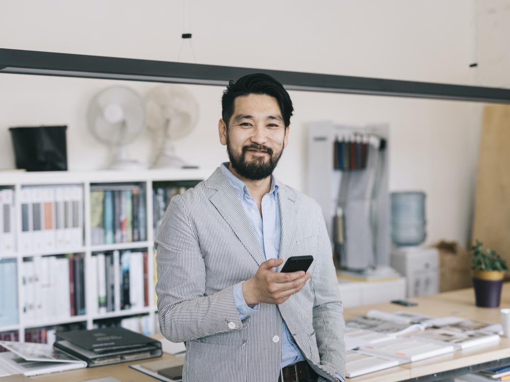 asian man smiling in office wearing striped blazer and holding phone