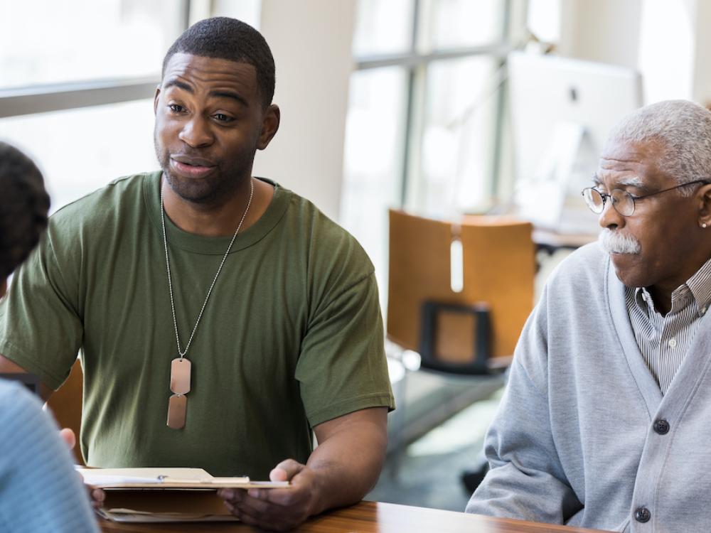 black veteran wearing dog tags sitting with older man at a desk