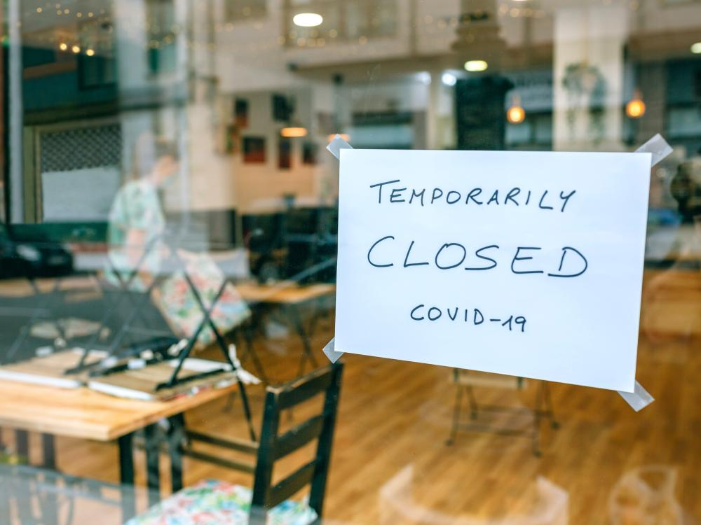restaurant with temporarily closed for COVID sign on door