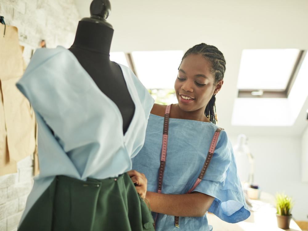 young black woman standing beside tailors dummy making dress