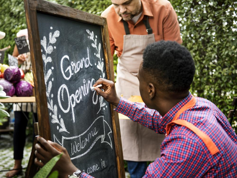 black man in plaid purple shirt writing Grand Opening on chalkboard for new marketplace