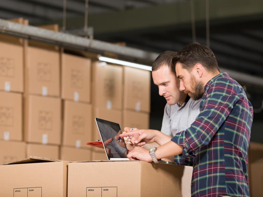 two business partners in a warehouse looking at a laptop on a stack of cardboard boxes