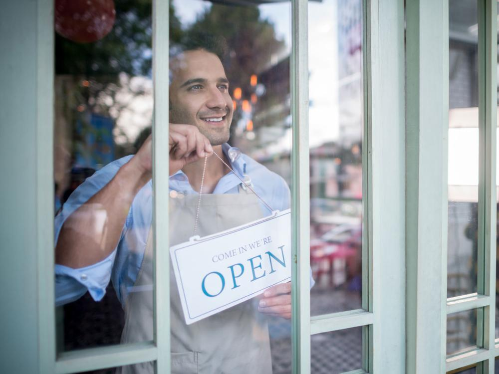 Business owner with Open sign.