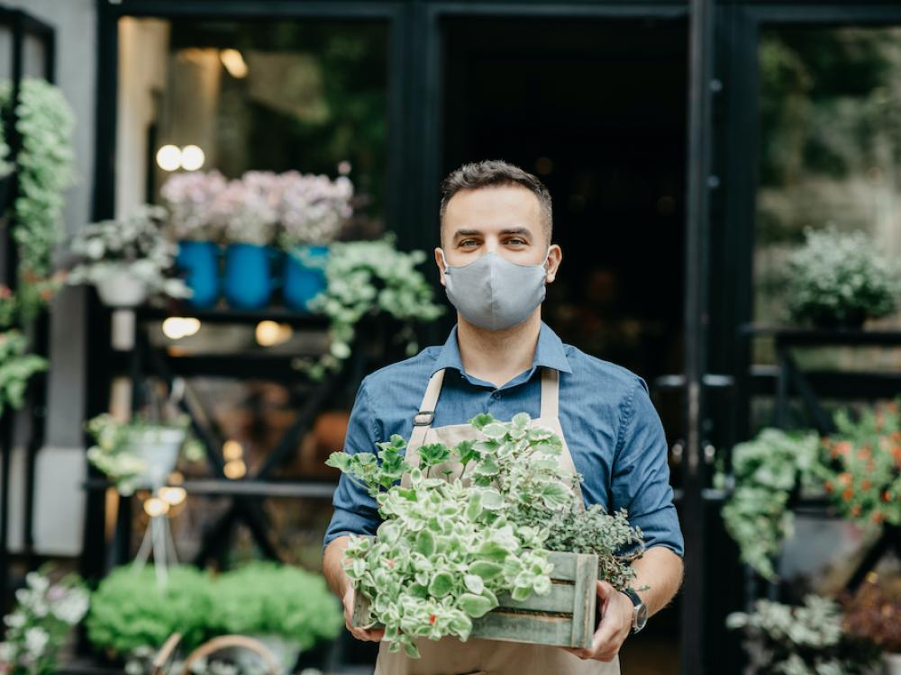 man holding box of succulents outside of business