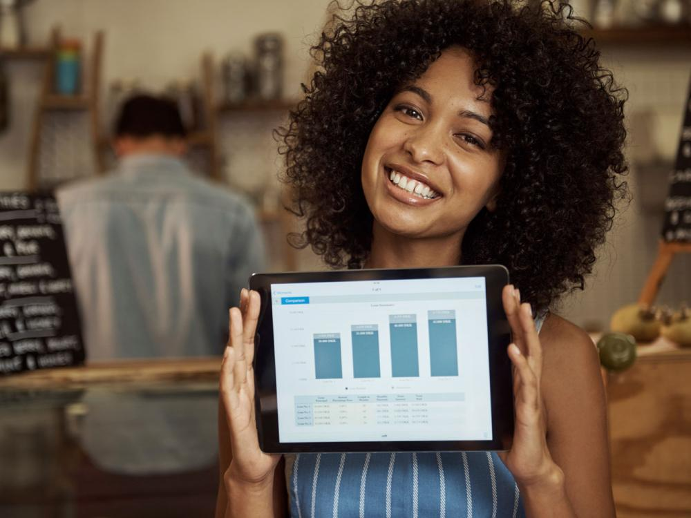 Woman holding tablet displaying graphs