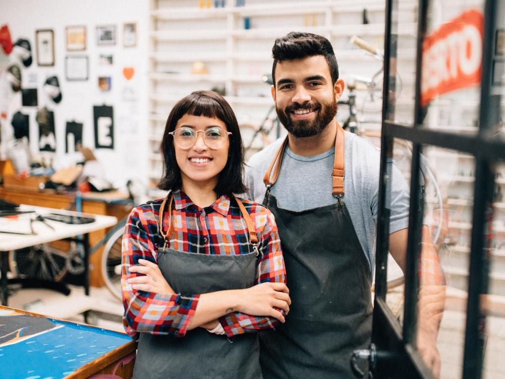 two small business owners standing in their shop wearing aprons