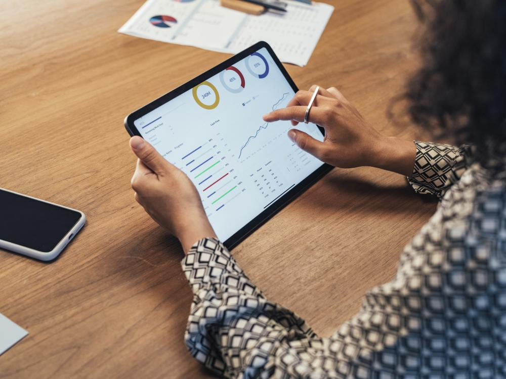 woman using tablet with graphs and analytics on it
