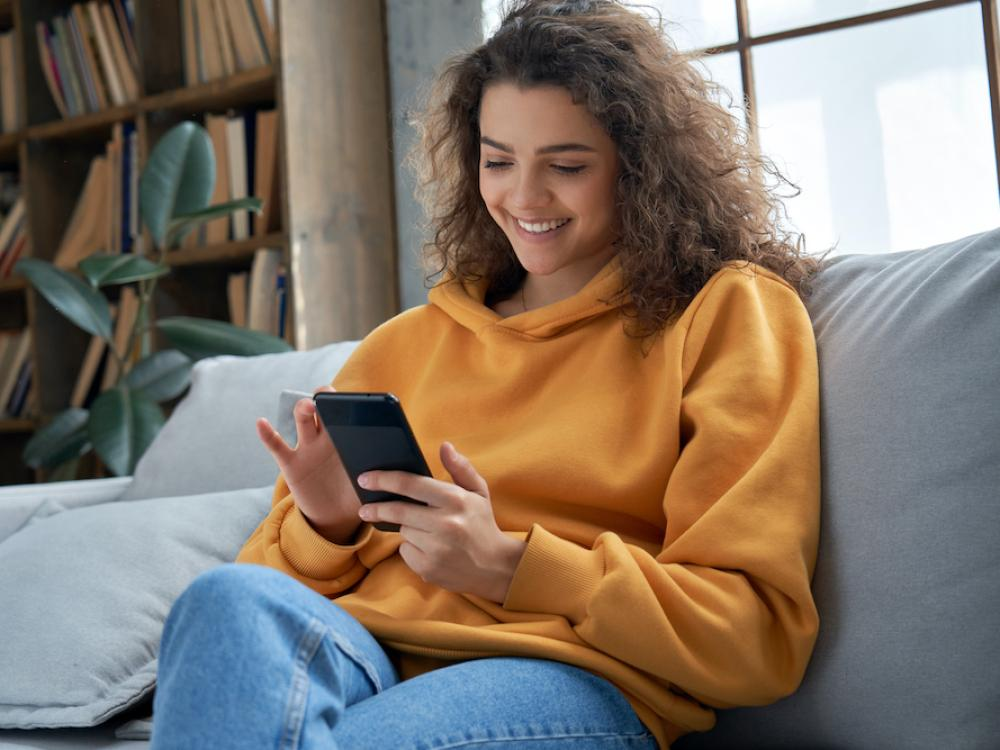 young hispanic woman texting on cell phone in orange sweater
