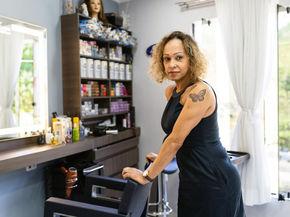 woman dressed in black dress standing behind hairdressers chair