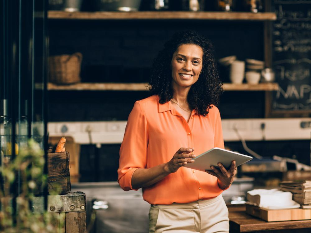 hispanic woman business owner in orange shirt holding tablet by desk