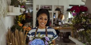 black business woman holding flowers and smiling