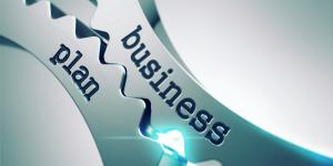 Photo of two interlocking gears with the words 'business' and 'plan' on each gear