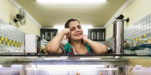 Latina behind the pastry counter of her business
