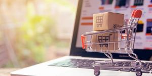Mini shopping cart filled with packages sitting on a laptop keyboard
