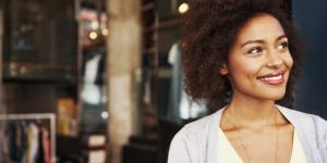 Female black business owner smiling in front of open business doors.