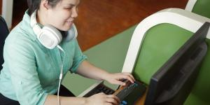 Young girl with a sight impairment using a computer with accessibility features.