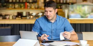 Man doing business finances on tablet with calculator