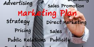 Photo of a businessman writing 'Marketing Plan' on a glass board, along with other marketing terms