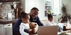 black man working at laptop while managing two small children and a teddy bear