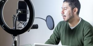 latino man in green sweater recording podcast with ring light and cellphone