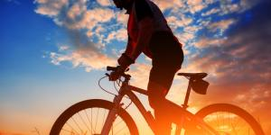 man rides bicycle in sun