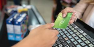 person gives loyalty card to cashier