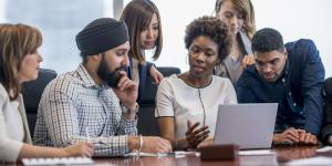 group of racially diverse people sitting and standing around a conference table