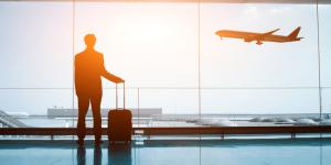 business man with luggage at airport watching plane