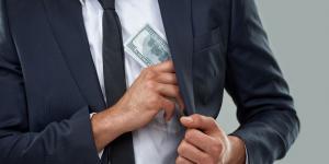 business man puts money in jacket