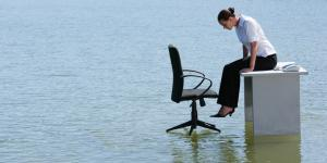 businesswoman sits on desk in flood