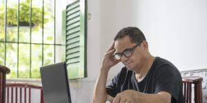 Hispanic man sitting at dining room table working on laptop next to open window