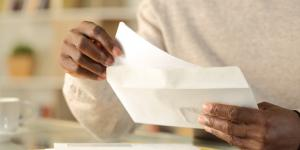 hands of black man putting paper into an envelope