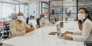 coworkers sit in conference room wearing masks