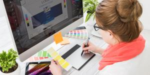 white woman working on a logo for a small business holding yellow paint chip