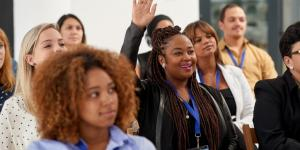 woman raising hand in conference