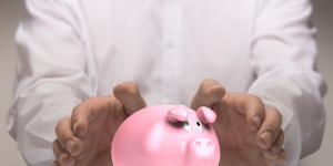 hands protect piggy bank