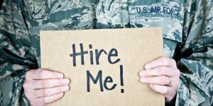 veteran holding hire me sign